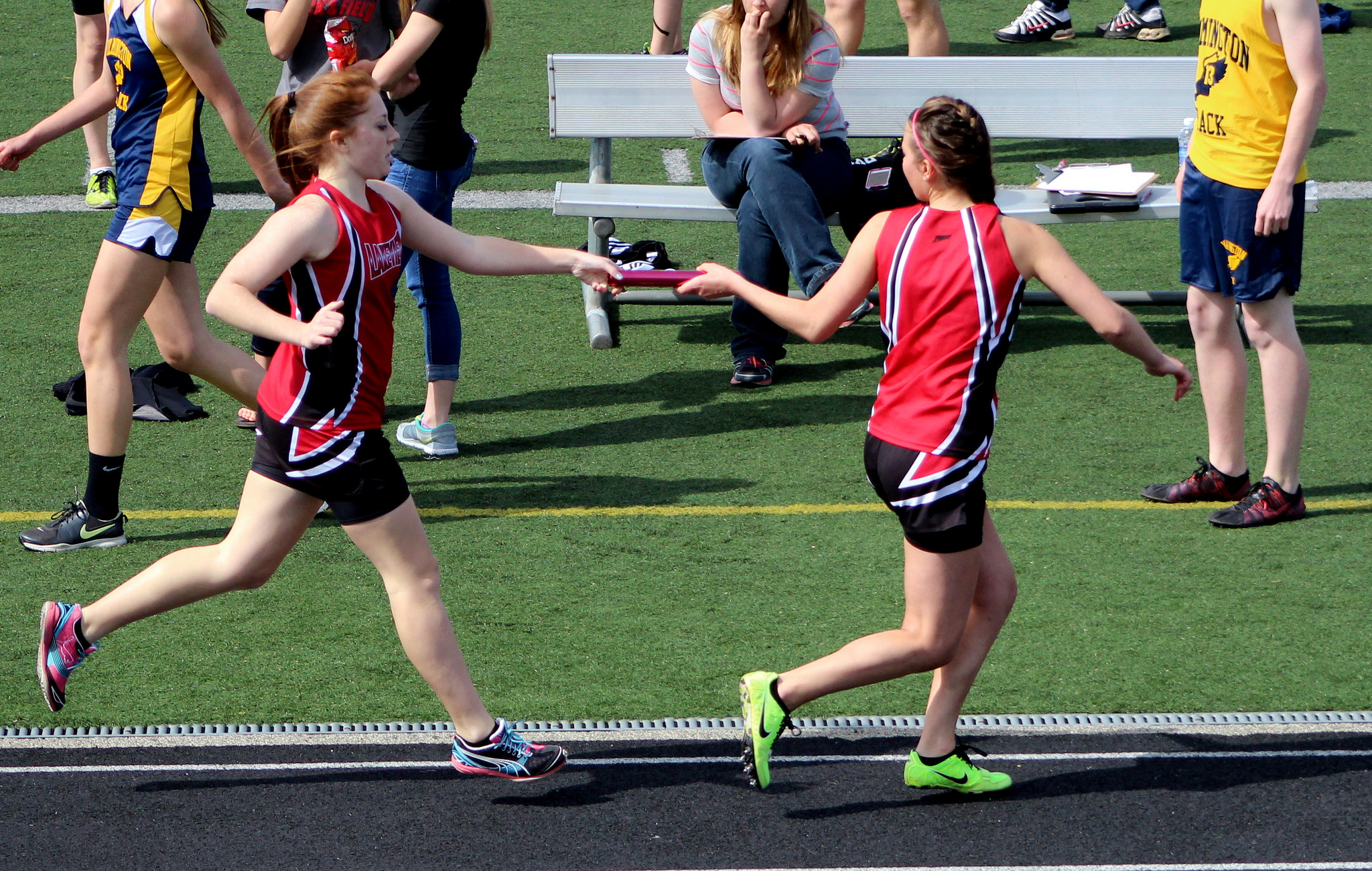runners in black and red uniforms passing baton