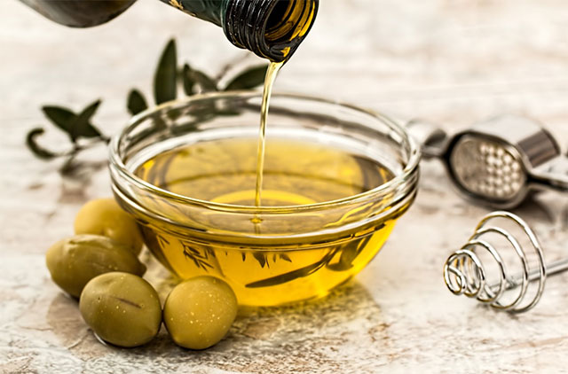 Pouring olive oil on a bowl